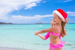 Little adorable girls in Santa hats during beach Stock Image