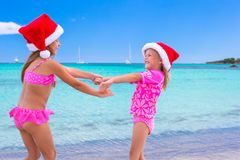 Little adorable girls in Santa hats during beach Royalty Free Stock Photos