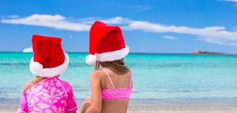 Little adorable girls in Santa hats during beach Royalty Free Stock Image
