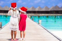 Little adorable girls in Santa hats during beach Stock Photo