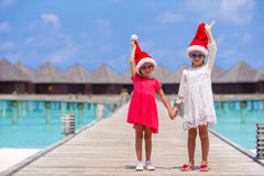 Little adorable girls in Santa hats during beach Stock Images