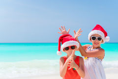 Little adorable girls in Santa hats during beach vacation have fun together Royalty Free Stock Photo
