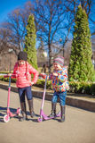 Little adorable girls with scooter in spring park at warm day Royalty Free Stock Photography