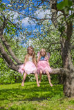 Little adorable girls sitting on blossoming apple Royalty Free Stock Photos