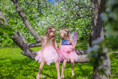 Little adorable girls sitting on blossoming tree Stock Photos