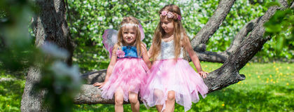Little adorable girls sitting on blossoming tree Stock Photography