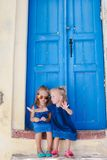 Little adorable girls sitting near old blue door Stock Photos