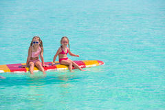 Little adorable girls on a surfboard in the Stock Photos