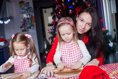 Little adorable girls and young mother baking Stock Photo