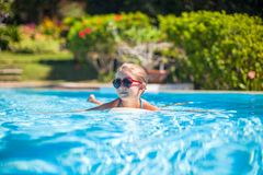 Little adorable happy girl swims in the swimming Royalty Free Stock Photography