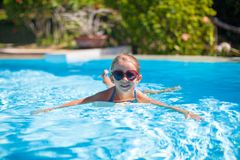 Little adorable happy girl swims in the swimming Royalty Free Stock Image