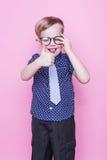 Little adorable kid in tie and glasses. School. Preschool. Fashion. Studio portrait over pink background. Little adorable boy in tie and glasses. School stock image
