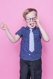 Little adorable kid in tie and glasses. School. Preschool. Fashion. Studio portrait over pink background. Little adorable boy in tie and glasses. School stock photography