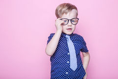 Little adorable kid in tie and glasses. School. Preschool. Fashion. Studio portrait over pink background. Little adorable boy in tie and glasses. School royalty free stock image