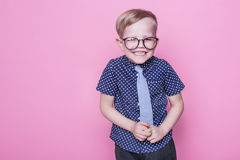 Little adorable kid in tie and glasses. School. Preschool. Fashion. Studio portrait over pink background. Little adorable boy in tie and glasses. School royalty free stock photo