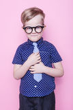 Little adorable kid in tie and glasses. School. Preschool. Fashion. Studio portrait over pink background. Stylish boy in shirt and glasses with big smile. School royalty free stock photos