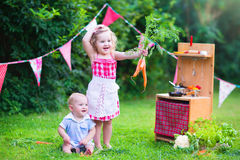 Little adorable kids playing with toy kitchen in the garden. Funny curly little girl and adorable baby boy, cute brother and sister, playing together with a Royalty Free Stock Image