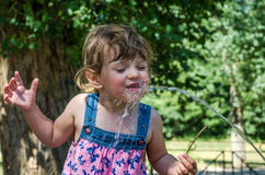 A little adorable little girl, a baby in a dress, drinks water from a spout of a Roman drinking fountain on a hot summer day, quen. Ching thirst, in the park at royalty free stock photo