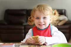The little adorable smiling blonde curly hair girls is eating breakfast. She holds a bread and smiles. stock photo