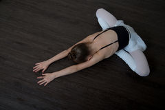 A little adorable young ballerina doing stretching exercises Stock Photo