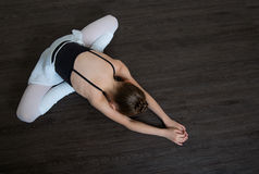 A little adorable young ballerina doing stretching exercises on Stock Photography