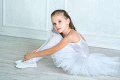 A little adorable young ballerina in a playful mood in the inter. Ior studio posing on camera Royalty Free Stock Photo