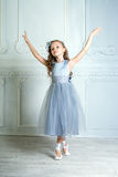 A little adorable young ballerina in a playful mood in the inter Stock Photos