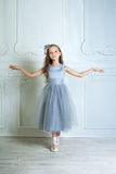A little adorable young ballerina in a playful mood in the inter Stock Image