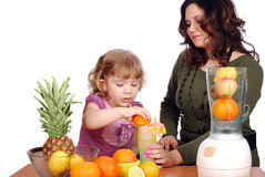 Little and adult girl made fruit juice Stock Photos
