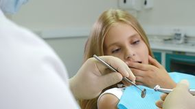 Little afraid girl at dentist office. Health and dental care. Closeup shot of dentist with drill and mirror in hands. 4K. Footage stock video