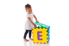 Little African American baby girl playing with construction game Stock Photos