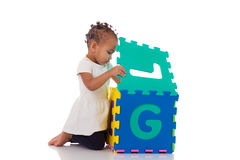 Little African American baby girl playing with construction game Stock Photo