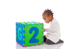 Little African American baby girl playing with construction game Royalty Free Stock Images
