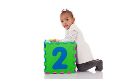 Little African American baby girl playing with construction game Stock Image