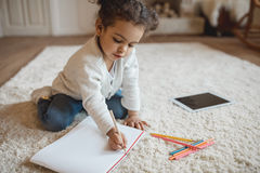 Little african american girl drawing with pencils and lying on carpet at home royalty free stock photos