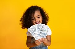 Free Little African-american Girl Holding Money, Yellow Background Stock Image - 156233861