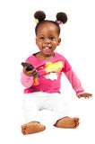 Little african american girl with mobile phone. Cute little African American child in pink holding mobile phone smiling, isolated stock image