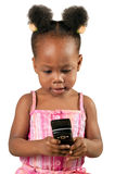 Little african american girl with mobile phone. Cute little African American child in pink looking at mobile phone, isolated royalty free stock images