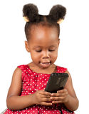 Little african american girl with mobile  phone. Cute little African American child in red looking at mobile phone, isolated Stock Images