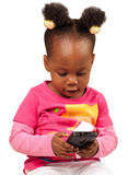 Little Girl in Pink with Mobile Phone. Cute little African American child in pink looking at mobile phone, isolated royalty free stock images
