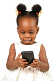 Little girl smiling at a mobile phone. Little African American girl with mobile phone and smiling royalty free stock photos