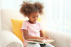 Little African American girl sitting in armchair and  reading book in room. Little African American girl sitting in armchair and reading book in room Stock Photography