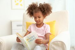 Little African American girl sitting in armchair and  reading book in room Stock Images