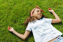 Little african american girl sleeping on green grass Royalty Free Stock Photos