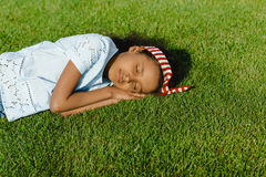 Little african american girl sleeping on green grass Royalty Free Stock Photography