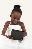 Little african american girl using a digital table. Little African American girl using a tablet PC on white background stock photos