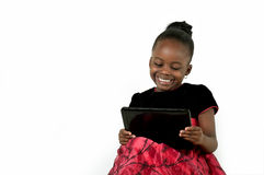 Little african american girl using a digital table. Little African American girl using a tablet PC on white background royalty free stock photo