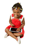 Little African American girl using tablet pc. Little African American girl using a tablet pc, isolated on white background Royalty Free Stock Image