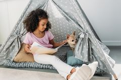 Little african american kid reading book with chihuahua dog near by in teepee. At home stock photo