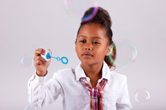 Little African Asian girl blowing soap bubbles Stock Photos